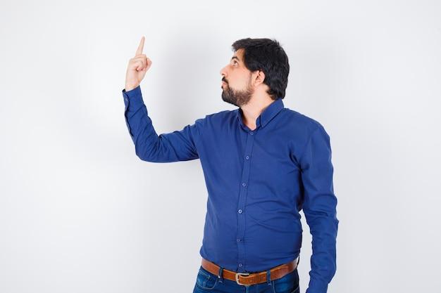Varón joven apuntando hacia arriba en camisa, jeans y mirando confiado, vista frontal.