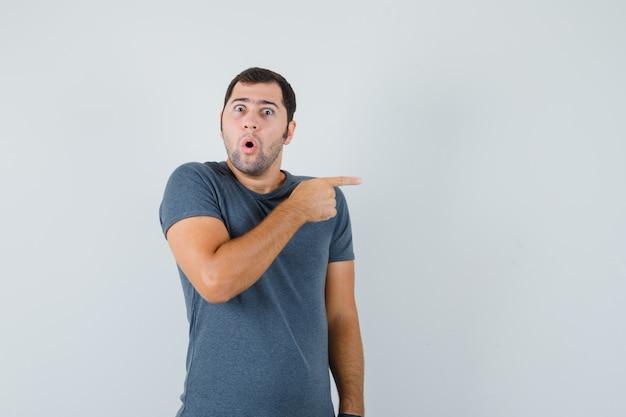 Varón joven apuntando hacia el lado en camiseta gris y mirando sorprendido