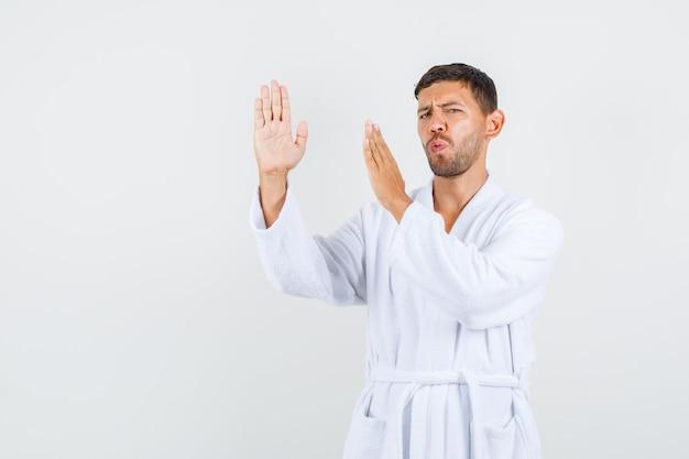 Varón joven en bata de baño blanca que muestra el gesto de chuleta de karate, vista frontal