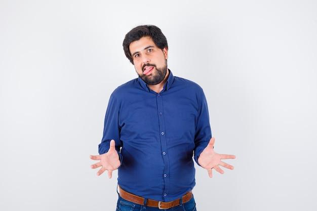 Varón joven en camisa azul real abriendo sus palmas mientras saca la lengua y se ve extraño, vista frontal.