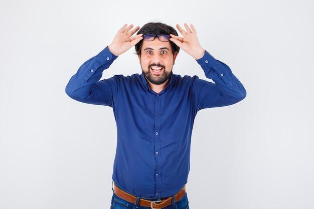 Varón joven en camisa azul real con gafas y mirando alegre, vista frontal.