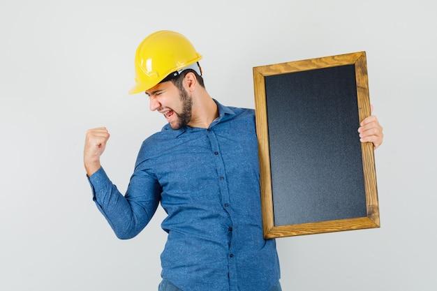 Varón joven en camisa, casco sosteniendo la pizarra, mostrando el gesto del ganador y mirando dichoso, vista frontal.