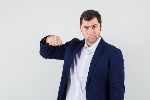 Varón joven en camisa, chaqueta amenazando con el puño y mirando rencoroso