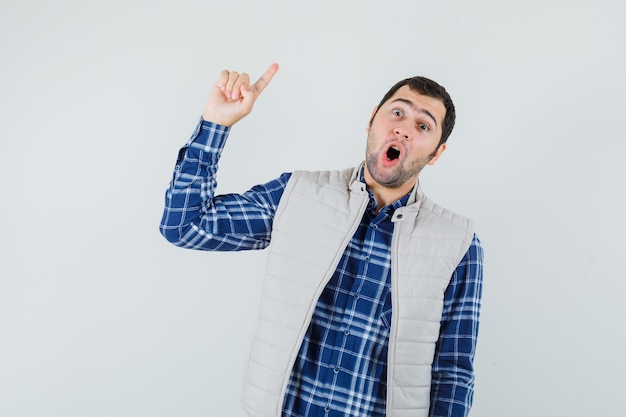 Varón joven en camisa, chaqueta apuntando hacia arriba mientras habla algo y mira aterrorizado, vista frontal.