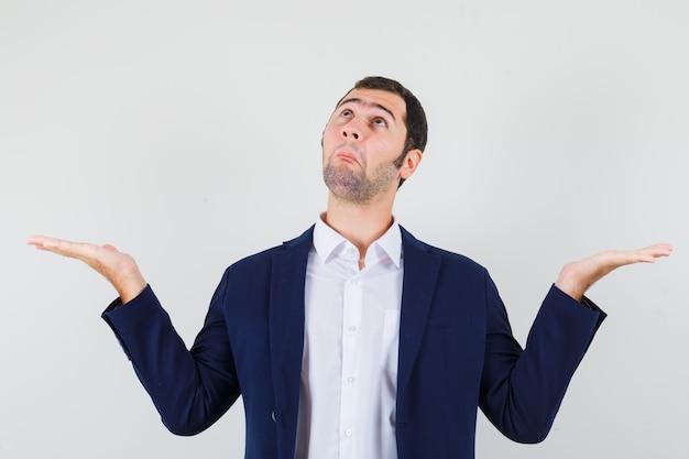 Varón joven en camisa, chaqueta extendiendo las palmas, mirando hacia arriba y mirando confundido