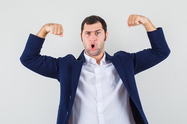 Varón joven en camisa, chaqueta mostrando los músculos de los brazos y mirando rencoroso