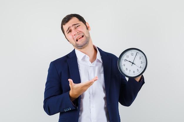 Varón joven en camisa y chaqueta mostrando reloj de pared y mirando melancólico