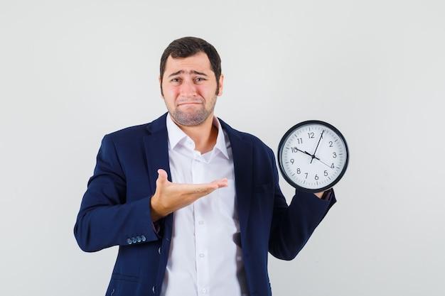 Varón joven en camisa y chaqueta mostrando reloj de pared y mirando triste