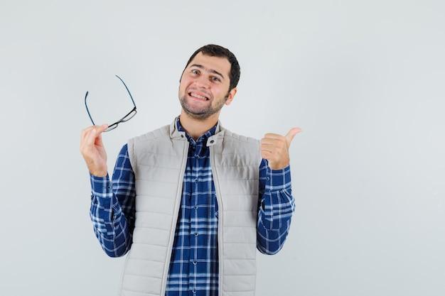 Varón joven en camisa, chaqueta sosteniendo gafas mientras muestra el pulgar hacia arriba y se ve positivo, vista frontal.