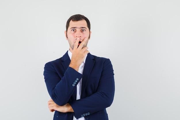 Varón joven en camisa y chaqueta sosteniendo la mano en la boca y mirando sorprendido