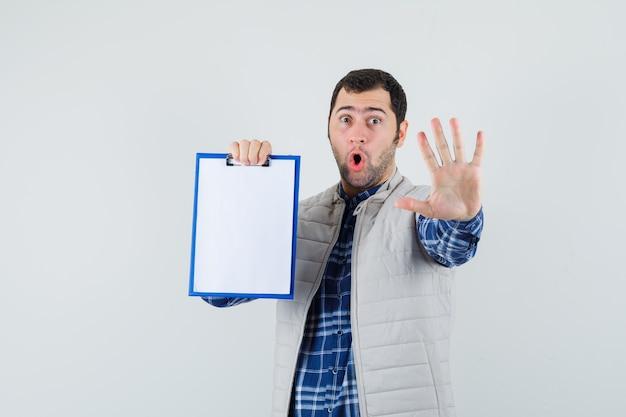 Varón joven en camisa, chaqueta sosteniendo el portapapeles mientras muestra el gesto de parada y mira asustado, vista frontal.