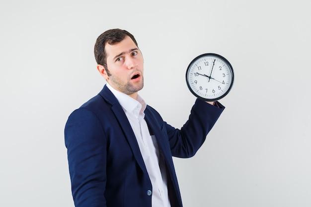 Varón joven en camisa y chaqueta sosteniendo el reloj de pared y mirando sorprendido