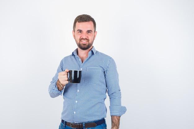 Varón joven en camisa, jeans sosteniendo la taza mientras está de pie y mirando alegre, vista frontal.