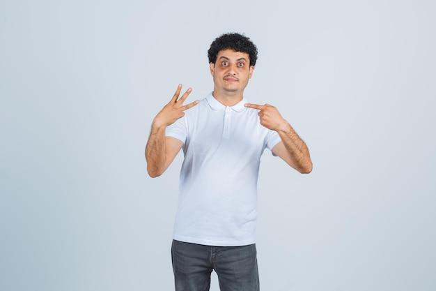 Varón joven en camiseta blanca, pantalones apuntando al número tres y mirando confiado, vista frontal.