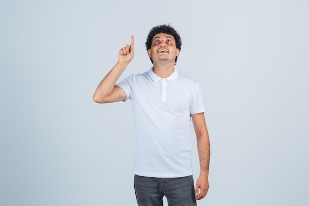 Varón joven en camiseta blanca, pantalones apuntando hacia arriba y mirando agradecido, vista frontal.