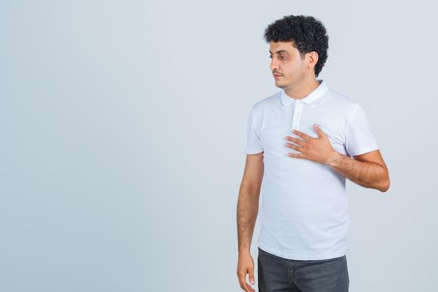 Varón joven en camiseta blanca, pantalones manteniendo la mano en el pecho y mirando pensativo, vista frontal.