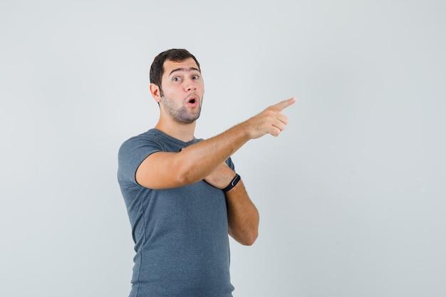 Varón joven en camiseta gris apuntando hacia afuera y mirando sorprendido