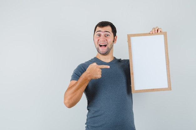 Varón joven en camiseta gris apuntando al marco vacío y mirando alegre