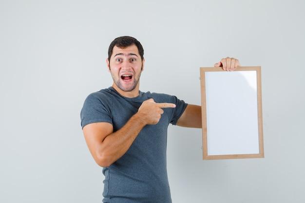 Varón joven en camiseta gris apuntando al marco vacío y mirando feliz