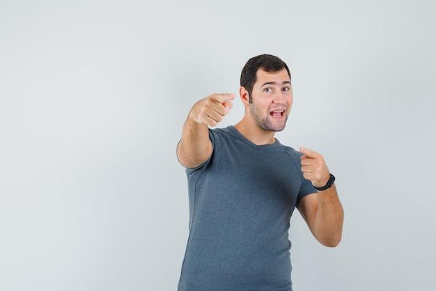 Varón joven en camiseta gris apuntando a la cámara y mirando confiado