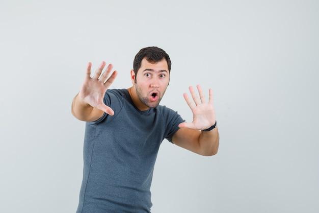 Varón joven en camiseta gris cogidos de la mano para defenderse y mirando asustado