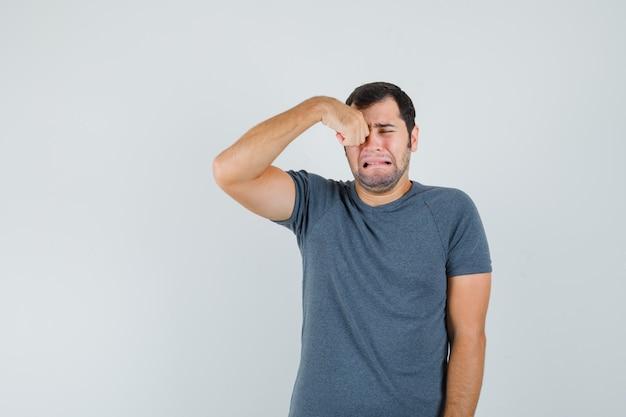Varón joven en camiseta gris frotándose los ojos mientras llora y parece ofendido