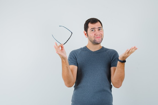 Varón joven en camiseta gris con gafas extendiendo la palma y mirando optimista