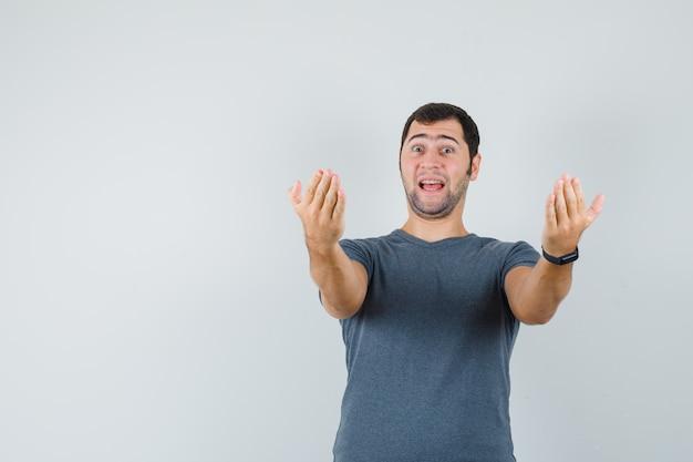 Varón joven en camiseta gris invitando a venir y mirando emocionado