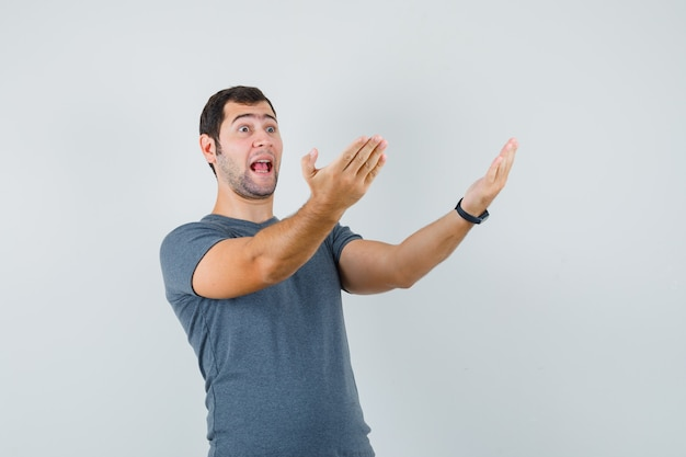Varón joven en camiseta gris invitando a venir y mirando jovial