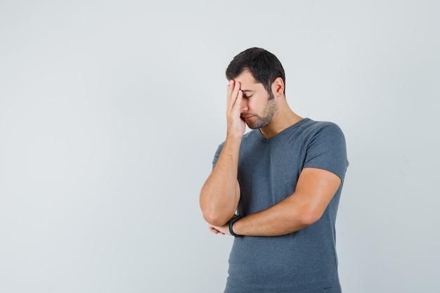 Varón joven en camiseta gris manteniendo la mano en la cara y con aspecto cansado