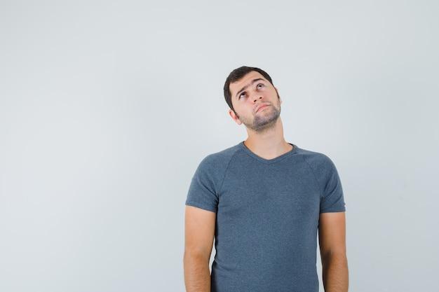 Varón joven en camiseta gris mirando hacia arriba y mirando pensativo