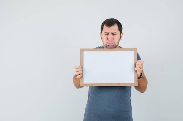 Varón joven en camiseta gris sosteniendo el marco vacío y mirando molesto