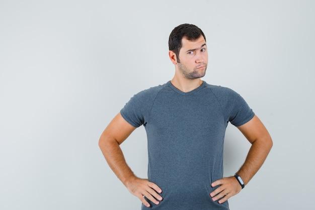 Varón joven en camiseta gris tomados de la mano en la cintura y mirando vacilante