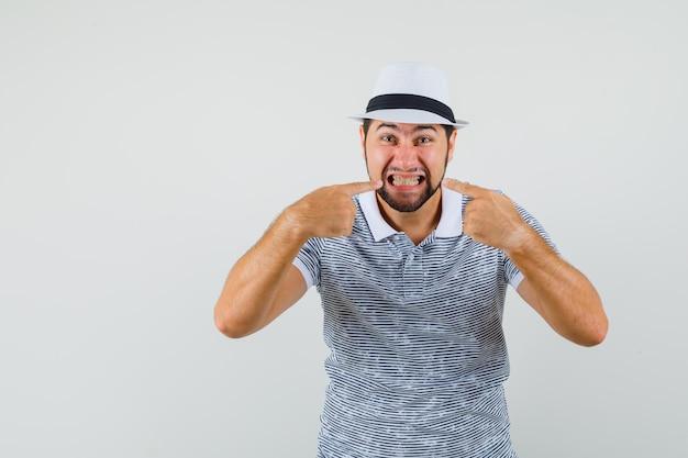 Varón joven en camiseta, sombrero apuntando a sus dientes apretados y mirando extraño, vista frontal.