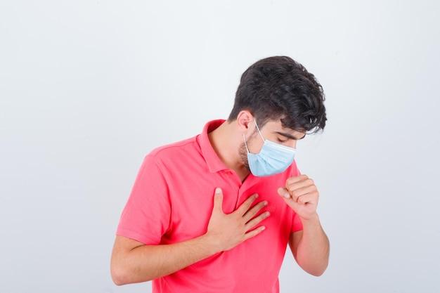Varón joven en camiseta tosiendo mientras sostiene la mano en el pecho y se ve mal, vista frontal.