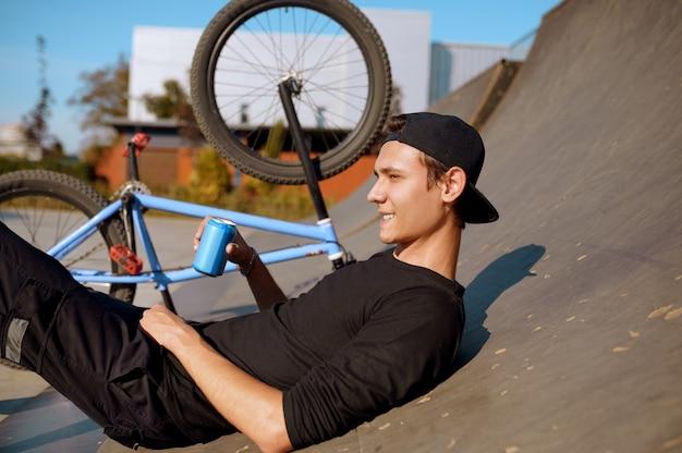 Varón joven ciclista de bmx ocios en rampa, adolescente en formación en skatepark. deporte extremo en bicicleta, ejercicio de ciclo peligroso, riesgo de montar en la calle, andar en bicicleta en el parque de verano