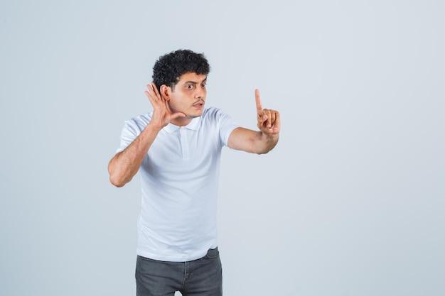 Varón joven escuchando una conversación privada, apuntando hacia arriba con camiseta blanca, pantalones y mirando sorprendido, vista frontal.