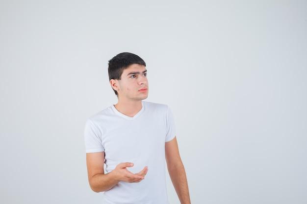 Varón joven estirando la mano en gesto de interrogación en camiseta y mirando pensativo, vista frontal.