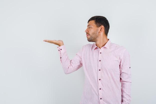 Varón joven extendiendo la palma a un lado en camisa rosa y mirando enfocado vista frontal.