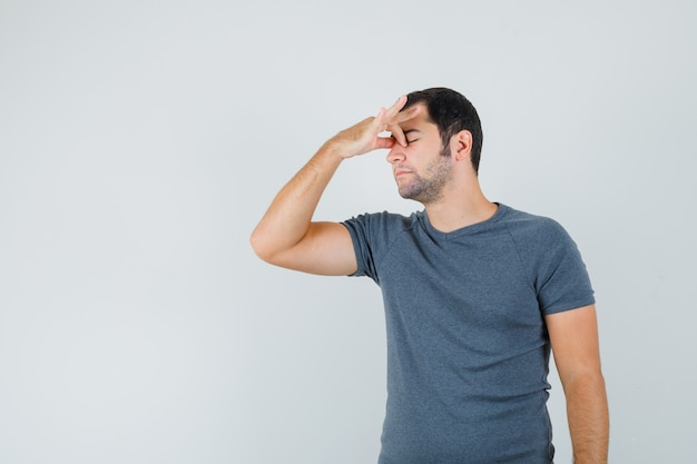 Varón joven frotándose los ojos y la nariz en una camiseta gris y con aspecto cansado. vista frontal.