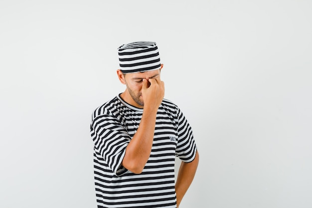 Varón joven frotándose los ojos y la nariz con un sombrero de camiseta a rayas y luciendo fatigado
