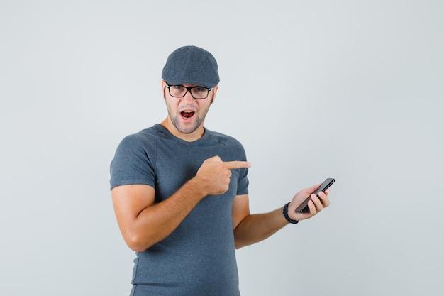 Varón joven en gorra de camiseta gris apuntando al teléfono móvil y mirando asombrado