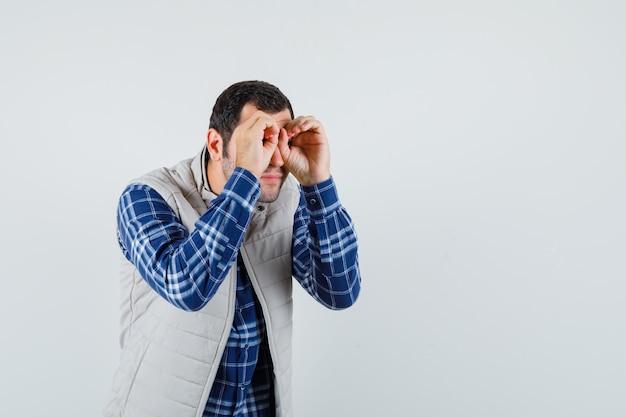 Varón joven haciendo gestos de binoculares en sus ojos en camisa, chaqueta sin mangas y mirando enfocado, vista frontal. espacio para texto