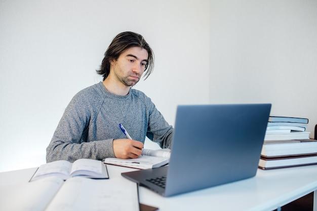 Varón joven hermoso que usa la computadora portátil en casa. estudiante aprende en la mesa. compras en línea, trabajo a domicilio, autónomo, aprendizaje en línea, concepto de estudio. educación a distancia