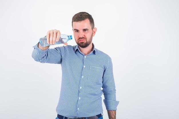 Varón joven inclinando la botella de agua de plástico en camisa, jeans y mirando vacilante, vista frontal.