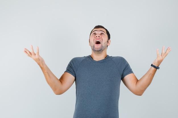 Varón joven levantando los brazos mirando hacia arriba en camiseta gris y mirando feliz