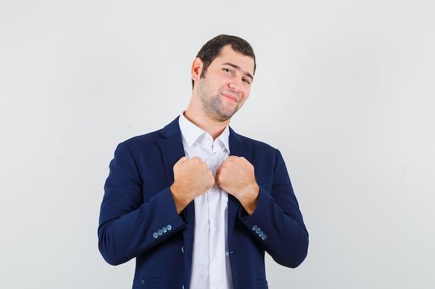 Varón joven manteniendo los puños en el pecho en camisa y chaqueta y mirando confiado