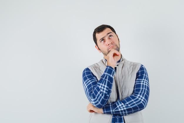 Varón joven mirando hacia arriba en camisa, chaqueta sin mangas y mirando pensativo, vista frontal. espacio para texto