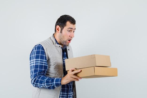 Varón joven mirando dentro de la caja en camisa, chaqueta y mirando sorprendido, vista frontal.