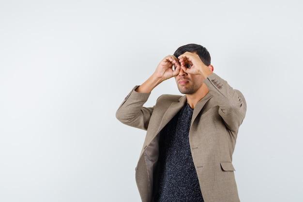 Varón joven mirando a otro lado mientras muestra el gesto de las gafas con los dedos en una chaqueta marrón grisácea, camisa negra y un aspecto extraño.